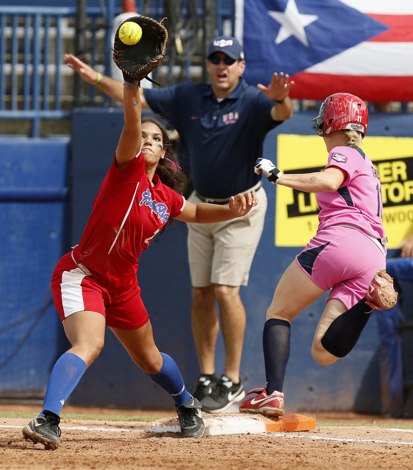 Photo - Taylor Thom (11) of the United States beats the throw to first base as Charlise Castro (21) makes the catch for Puerto Rico in the second inning during a game in the World Cup of Softball between the USA and Puerto Rico at ASA Hall of Fame Stadium in Oklahoma City, Sunday, July 14, 2013. Team USA won, 10-3 in five innings. Photo by Nate Billings, The Oklahoman