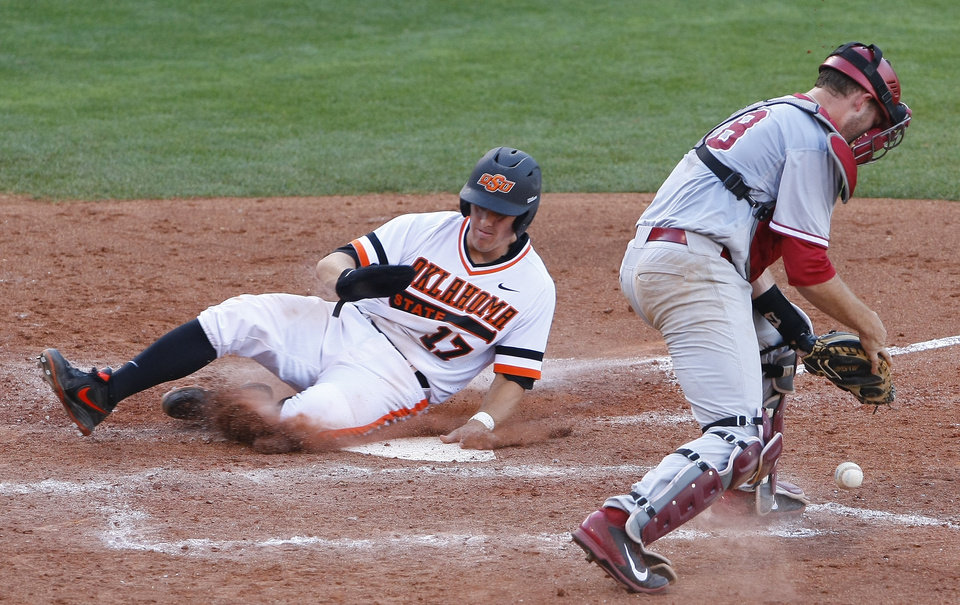 Photo - Oklahoma State's Gage Green (17) slides into home as Oklahoma's catcher Dylan Neal misses the throw to home in the bottom of the fith inning of a first-round game against Oklahoma State in the Big 12 conference NCAA college baseball tournament in Oklahoma City, Wednesday, May 21, 2014. (AP Photo/Alonzo Adams)