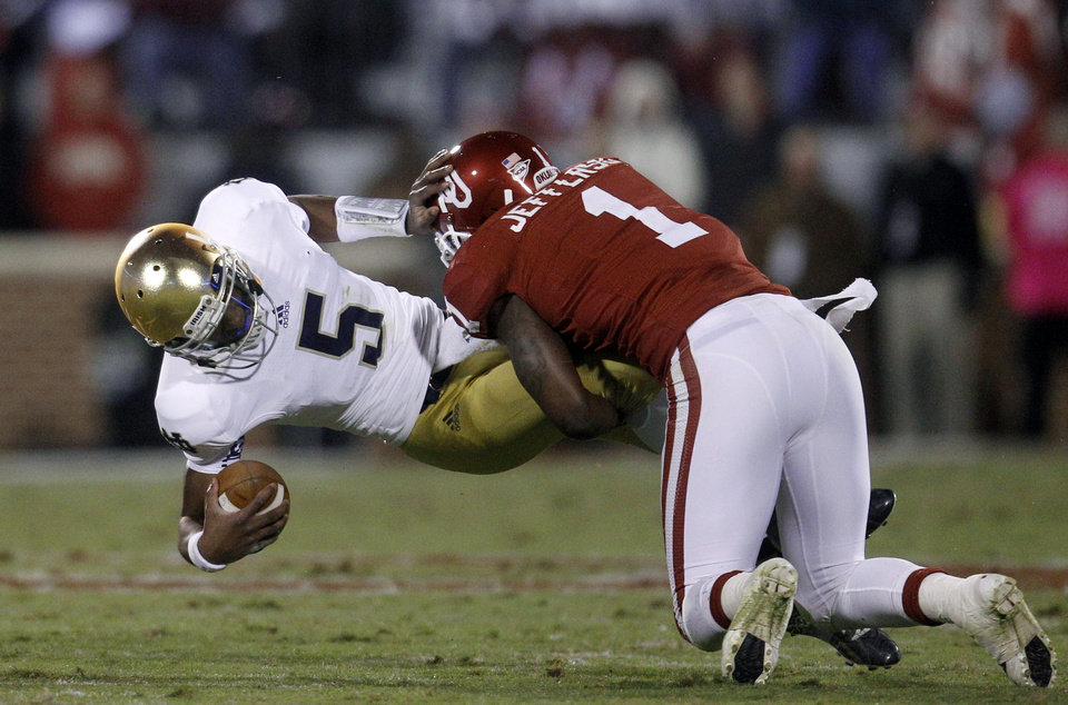 Photo -   Notre Dame quarterback Everett Golson is tackled by Oklahoma defender Tony Jefferson (1) in the third quarter of an NCAA college football game in Norman, Okla., Saturday, Oct. 27, 2012. (AP Photo/Sue Ogrocki)