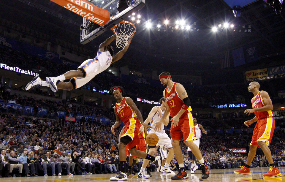 Oklahoma City's James Harden dunks the ball over Houston's Jordan Hill, left, and Brad Miller during the NBA basketball game between the Oklahoma City Thunder and the Houston Rockets at the Oklahoma City Arena on Wednesday, December 15,  2010.   Photo by Bryan Terry, The Oklahoman