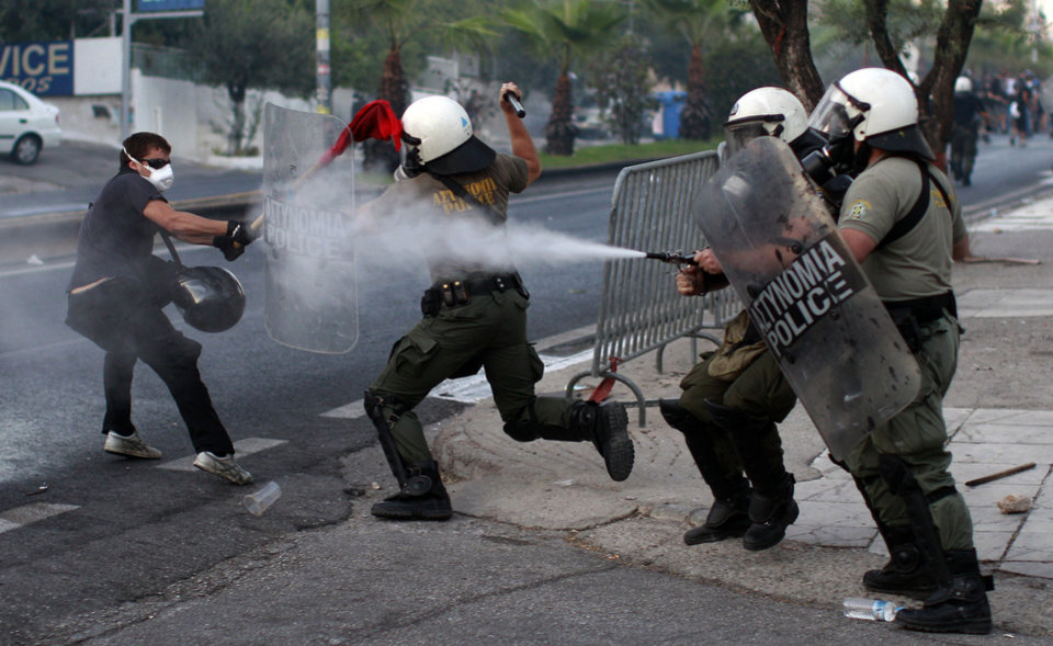 Photo - Protesters clash with Riot Police during a protest, after  the stabbing of a 34 year old man, in the suburb of Keratsini near Athens , Wednesday, Sept. 18,  2013. Violent clashes broke out Wednesday in several Greek cities after a member of the country's far-right Golden Dawn party was arrested in the fatal stabbing of a 34-year-old musician described as an anti-fascist activist. The stabbing drew condemnation from across Greece's political spectrum and from abroad. While the extremist Golden Dawn has been blamed for numerous violent attacks in the past, the overnight stabbing is the most serious violence directly attributed to a member so far. (AP Photo/Kostas Tsironis)