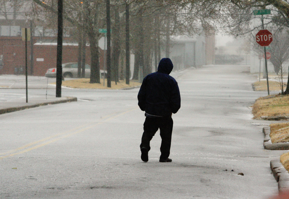A pedestrian walking down Francis Avenue from NW 6 Street on ice in Oklahoma City early Thursday morning, Dec. 24, 2009. Photo by Paul B. Southerland, The Oklahoman