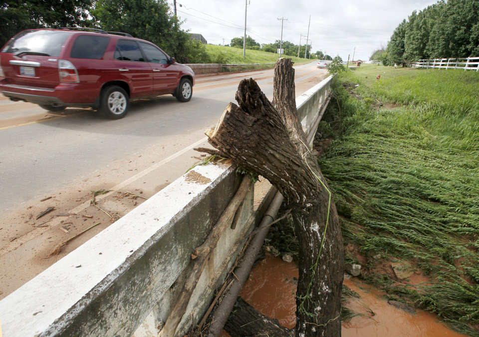 Photo - A large tree was deposited by floodwaters against this bridge on Santa Fe Ave. in Edmond, OK, Tuesday, June 15, 2010. By Paul Hellstern, The Oklahoman
