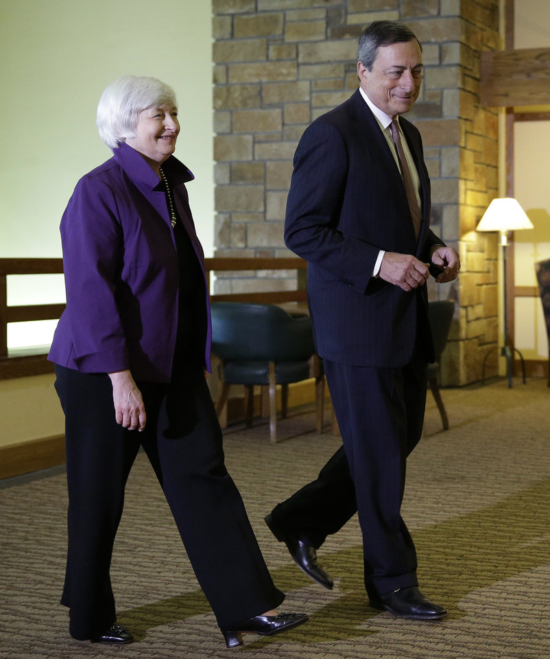 Photo - Federal Reserve Chair Janet Yellen, left, and European Central Bank President Mario Draghi walk together during the Jackson Hole Economic Policy Symposium at the Jackson Lake Lodge in Grand Teton National Park near Jackson, Wyo. Friday, Aug. 22, 2014. (AP Photo/John Locher)
