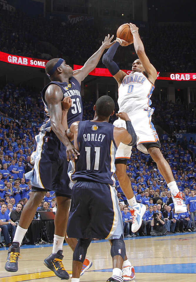 Photo - Oklahoma City's Russell Westbrook (0) puts up a shot over Memphis' Zach Randolph (50) and Mike Conley (11) during game one of the Western Conference semifinals between the Memphis Grizzlies and the Oklahoma City Thunder in the NBA basketball playoffs at Oklahoma City Arena in Oklahoma City, Sunday, May 1, 2011. Photo by Chris Landsberger, The Oklahoman