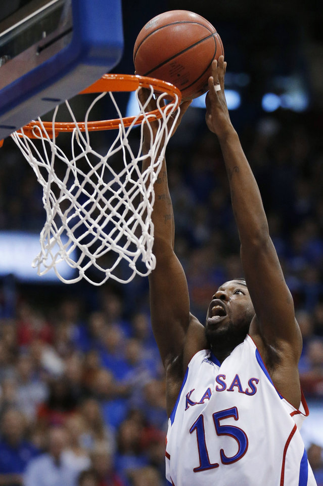 Photo - Kansas guard Elijah Johnson dunks during the first half of an NCAA college basketball game against Oklahoma State in Lawrence, Kan., Saturday, Feb. 2, 2013. (AP Photo/Orlin Wagner)