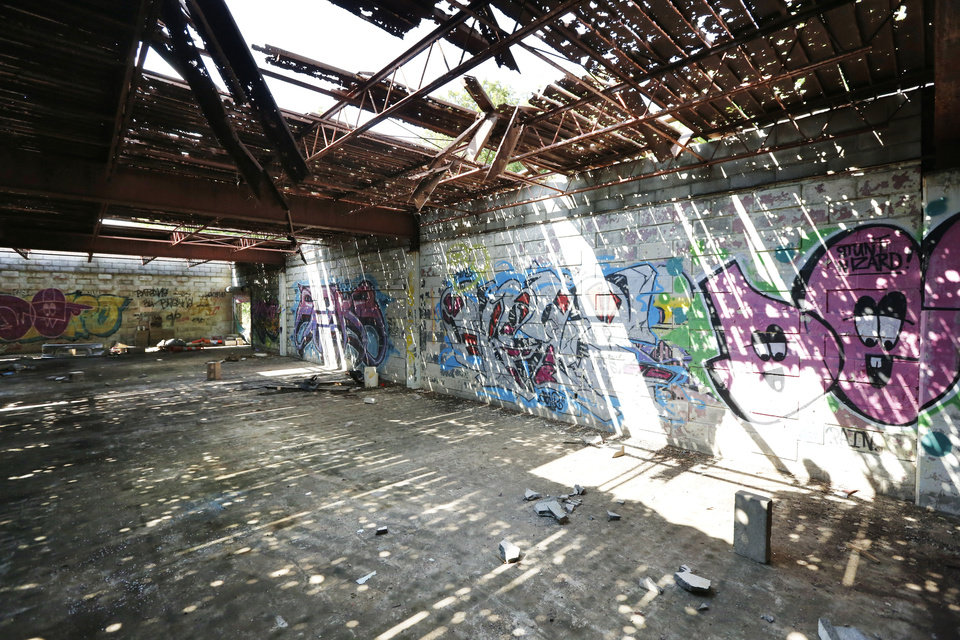 Photo -  Holes in the roof and graffiti on the walls attest to the neglect of the abandoned Bryant Center. [Photos by Paul Hellstern, The Oklahoman]