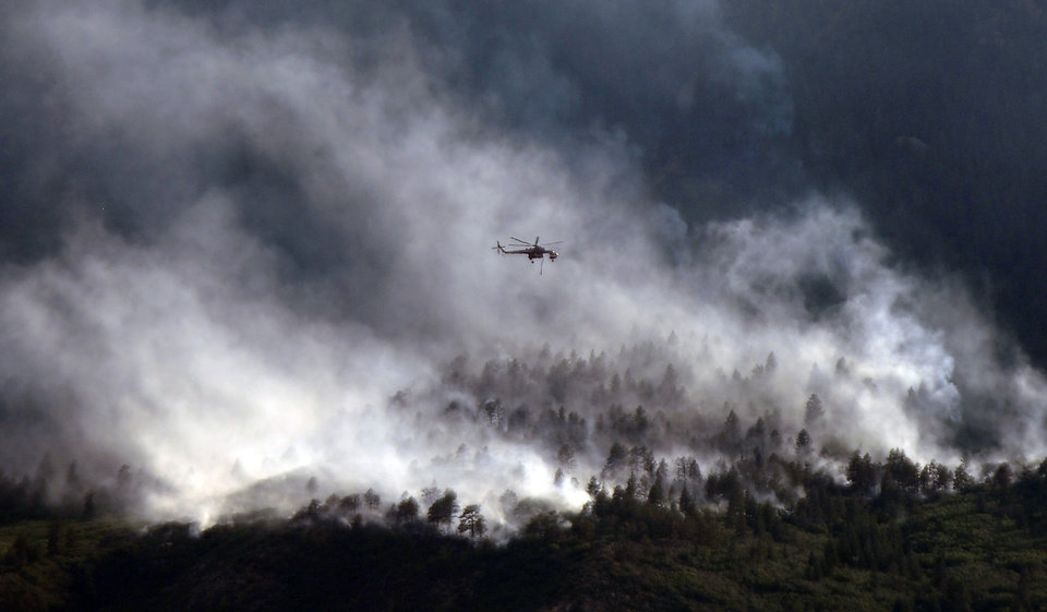 Photo -   A helicopters flies over as the Waldo Canyon Fire continues to burn Wednesday, June 27, 2012, in Colorado Springs, Colo. The wildfire doubled in size overnight to about 24 square miles (62 square kilometers), and has so far forced mandatory evacuations for more than 32,000 residents. (AP Photo/Bryan Oller)
