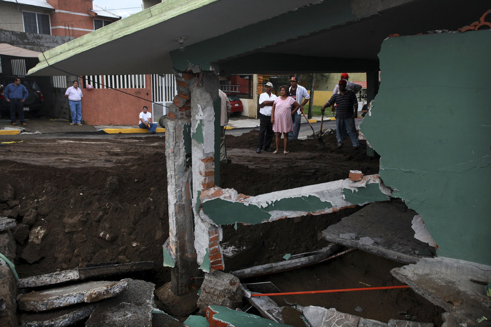 Photo - Neighbors look at the damage after part of a street and a home collapsed due to heavy rains in the Gulf port city of Veracruz, Mexico, Tuesday Sept. 2, 2014. The Gulf states of Mexico are bracing for more bad weather as Tropical Storm Dolly will cross the coast lat this evening or overnight and continue moving inland over northeastern Mexico on Wednesday. (AP Photo/Felix Marquez)