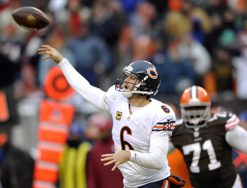 Photo - Chicago Bears quarterback Jay Cutler passes during the fourth quarter under pressure from Cleveland Browns defensive end Ahtyba Rubin during an NFL football game Sunday, Dec. 15, 2013, in Cleveland. Chicago won 38-31. (AP Photo/David Richard)