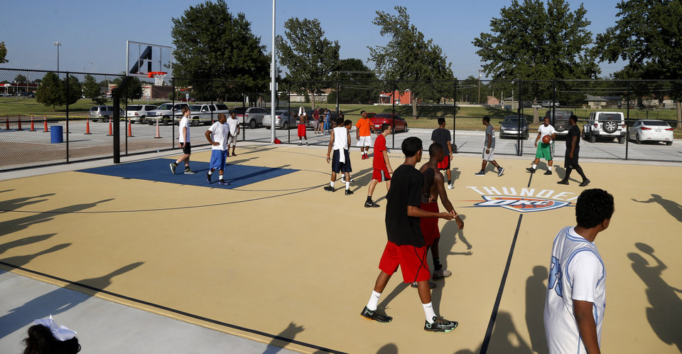 Photo -  Members of the crowd play on new public basketball courts during a grand opening ceremony in Midwest City. The two new courts called Thunder and Rumble feature new lighting, fencing and the Oklahoma City Thunder logo on soft surface flooring. Photo by Bryan Terry, The Oklahoman   BRYAN TERRY -  THE OKLAHOMAN