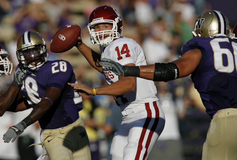 Photo - Oklahoma's Sam Bradford (14) looks to pass the ball under the defensive pressure from Washington during the first half of the college football game between the University of Oklahoma Sooners (OU) and the University of Washington Huskies (UW) at Husky Stadium on Saturday, Sep. 13, 2008, in Seattle, Wash. 