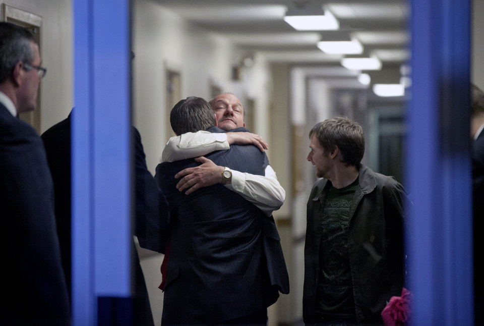 Photo - Randy Parker, facing camera, embraces his son Robbie Parker, the father of six-year-old Emilie who was killed in the Sandy Hook Elementary School shooting, before he addresses the media on the death of his daughter at a news conference, Saturday, Dec. 15, 2012, in Newtown, Conn. (AP Photo/David Goldman) ORG XMIT: CTDG126