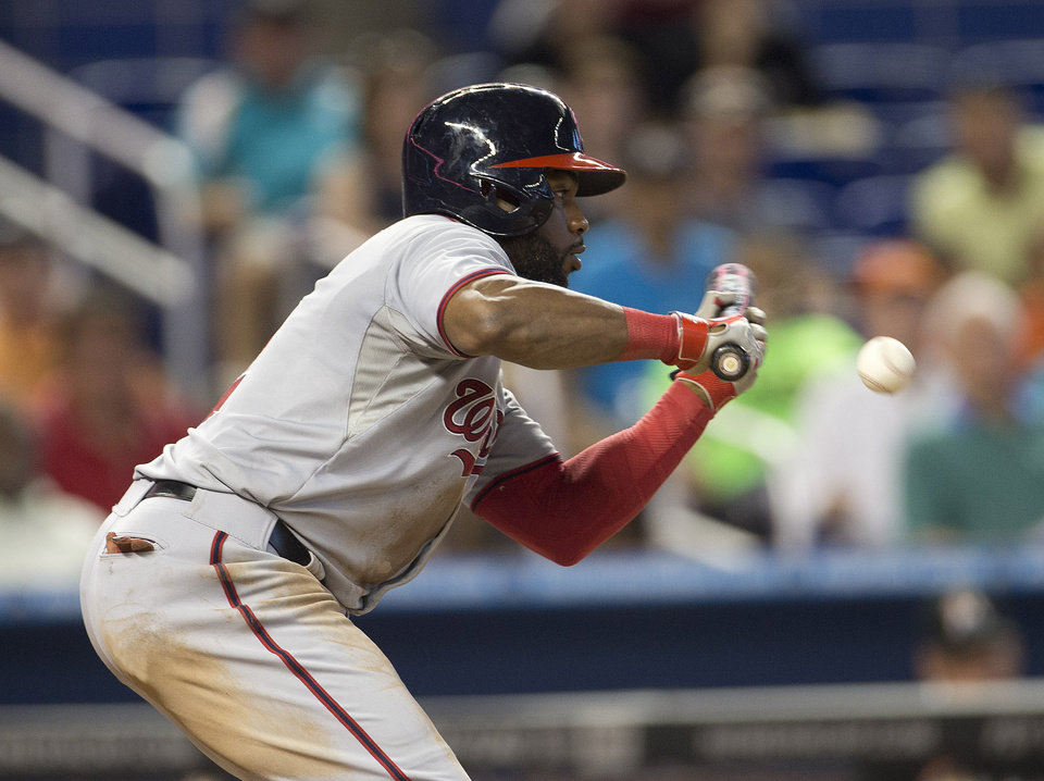 Photo - Washington Nationals batter Denard Span bunts during the eighth inning of a baseball game against the Miami Marlins, in Miami, Wednesday, July 30, 2014. The Nationals won 4-3. (AP Photo/J Pat Carter)