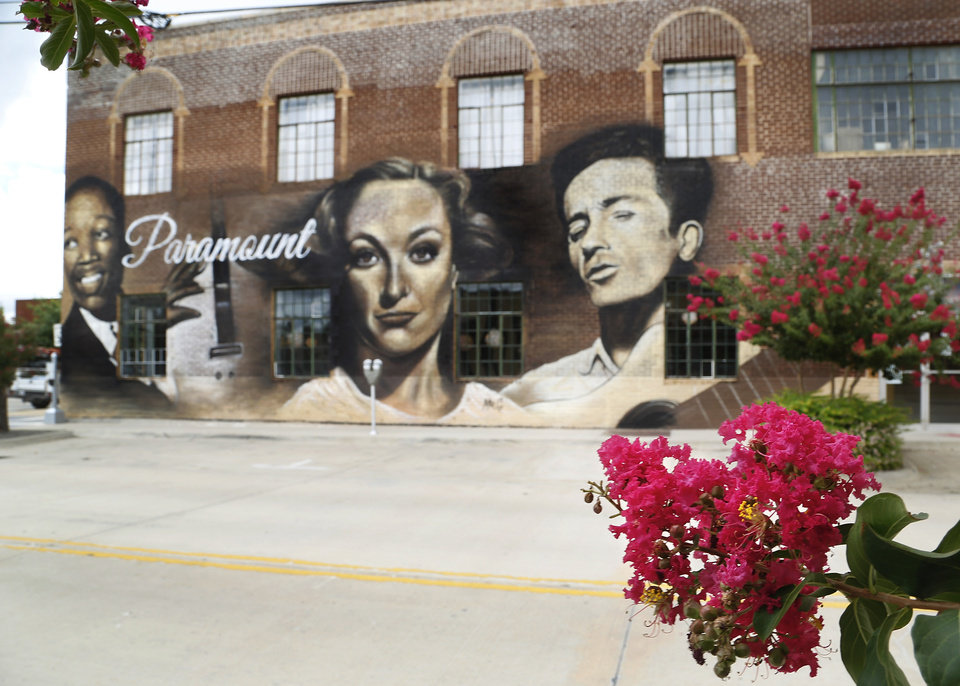 Photo - Murals on east wall of Paramount building in Film Row, 7 N. Lee Avenue. Photo taken Thursday, Aug. 18, 2016.  Faces, from left, are Charlie Christian, Joan Crawford and Woody Guthrie.  Photo by Jim Beckel, The Oklahoman