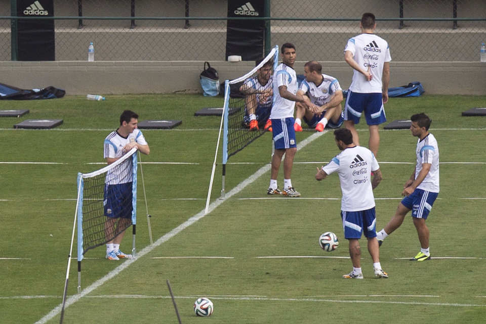 Photo - Argentina's Lionel Messi, left, talks to teammates Sergio Aguero, right, and Ezequiel Lavezzi, second right,  during a training session in Vespesiano, near Belo Horizonte, Brazil, Friday, July 11, 2014.  On Sunday, Argentina faces Germany for the World Cup final soccer match in Rio de Janeiro. (AP Photo/Victor R. Caivano)