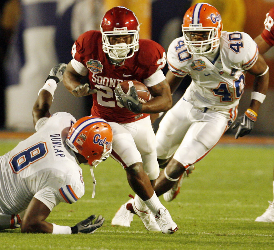 Photo - Oklahoma's Chris Brown (29) rushes past Florida's Carlos Dunlap (8) and Brandon Hicks (40) during the first half of the BCS National Championship college football game between the University of Oklahoma Sooners (OU) and the University of Florida Gators (UF) on Thursday, Jan. 8, 2009, at Dolphin Stadium in Miami Gardens, Fla. PHOTO BY NATE BILLINGS, THE OKLAHOMAN