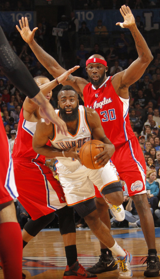 Photo - Oklahoma City Thunder guard James Harden (13) drives past Los Angeles Clippers power forward Reggie Evans (30) during the NBA basketball game between the Oklahoma City Thunder and the Los Angeles Clippers at Chesapeake Energy Arena on Wednesday, March 21, 2012 in Oklahoma City, Okla.  Photo by Chris Landsberger, The Oklahoman