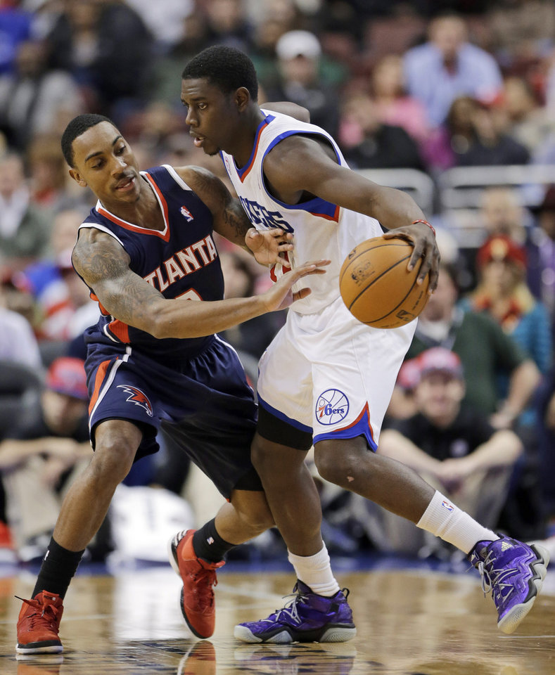 Photo - Philadelphia 76ers' Jrue Holiday, right, tries to keep the ball from Atlanta Hawks' Jeff Teague during the first half of an NBA basketball game, Friday, Dec. 21, 2012, in Philadelphia. (AP Photo/Matt Slocum)