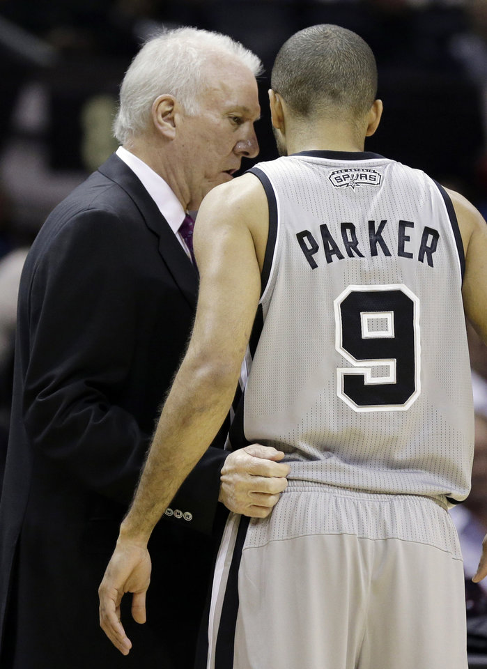 Photo - San Antonio Spurs coach Gregg Popovich, left, talks with Tony Parker during the first half of an NBA basketball game against the Cleveland Cavaliers, Saturday, Nov. 23, 2013, in San Antonio. (AP Photo/Eric Gay)