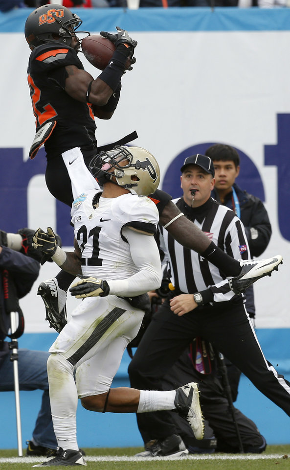 Photo - Oklahoma State's Isaiah Anderson (82) catches a touchdown pass  in front of Purdue's Ricardo Allen (21) during the Heart of Dallas Bowl football game between the Oklahoma State University (OSU) and Purdue University at the Cotton Bowl in Dallas,  Tuesday,Jan. 1, 2013. Photo by Sarah Phipps, The Oklahoman