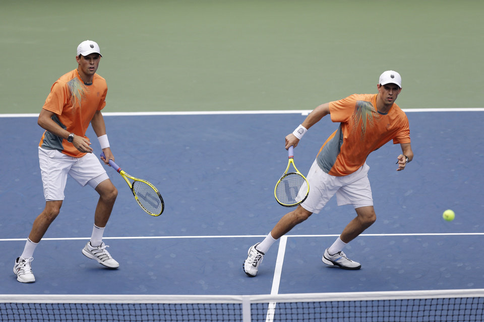 Photo -   Bob Bryan, left, and Mike Bryan during men's doubles play against Nicolas Mahut and Julien Benneteau of France at the 2012 US Open tennis tournament, Wednesday, Sept. 5, 2012, in New York. (AP Photo/Mike Groll)