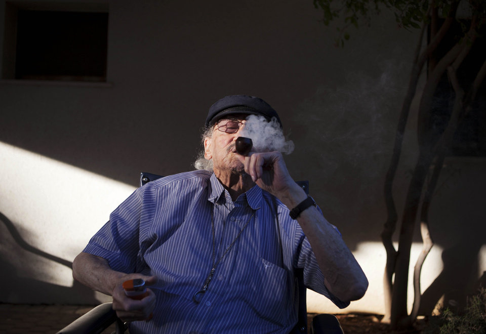 Photo -   In this photograph made on Tuesday, Oct. 30, 2012, Moshe Rute, 80, smokes medical cannabis at the old age nursery home in kibbutz Naan next to the city of Rehovot, Israel. Marijuana is illegal in Israel but medical use has been permitted since the early nineties for cancer patients and those with pain-related illnesses such as Parkinson's, Multiple Sclerosis, and even post-traumatic stress disorder. (AP Photo/Dan Balilty)
