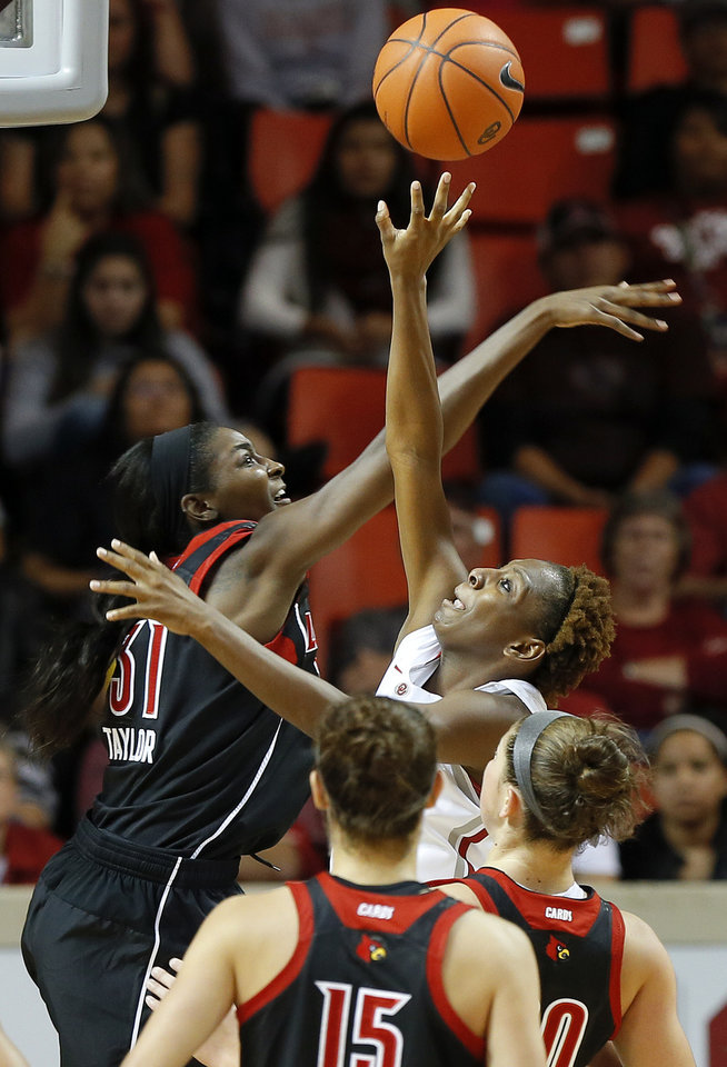 Photo - Oklahoma's Sharane Campbell, right, tries to get past Louisville's Asia Taylor during the first half of an NCAA college basketball game in Norman, Okla., Sunday, Nov. 17, 2013. (AP Photo/Bryan Terry)
