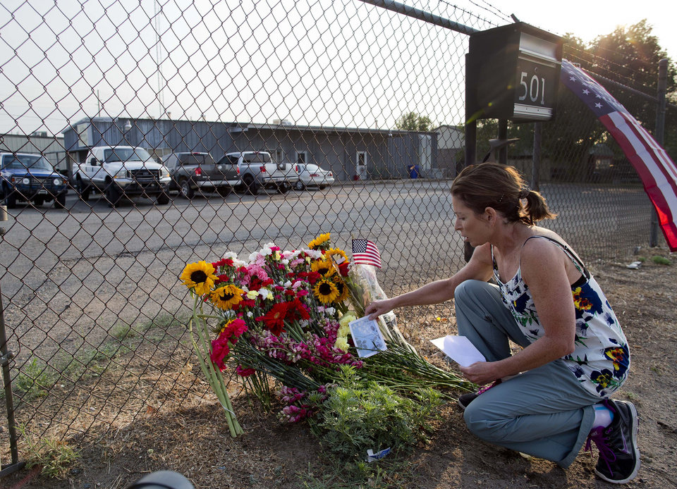 Photo - Toby Schultz lays flowers at the gate of the Granite Mountain Hot Shot Crew fire station, Monday, July 1, 2013, in Prescott, Ariz. An out-of-control blaze overtook the elite group of firefighters trained to battle the fiercest wildfires, killing 19 members as they tried to protect themselves from the flames under fire-resistant shields. The disaster Sunday afternoon all but wiped out the 20-member Hotshot fire crew leaving the city's fire department reeling. (AP Photo/Julie Jacobson)