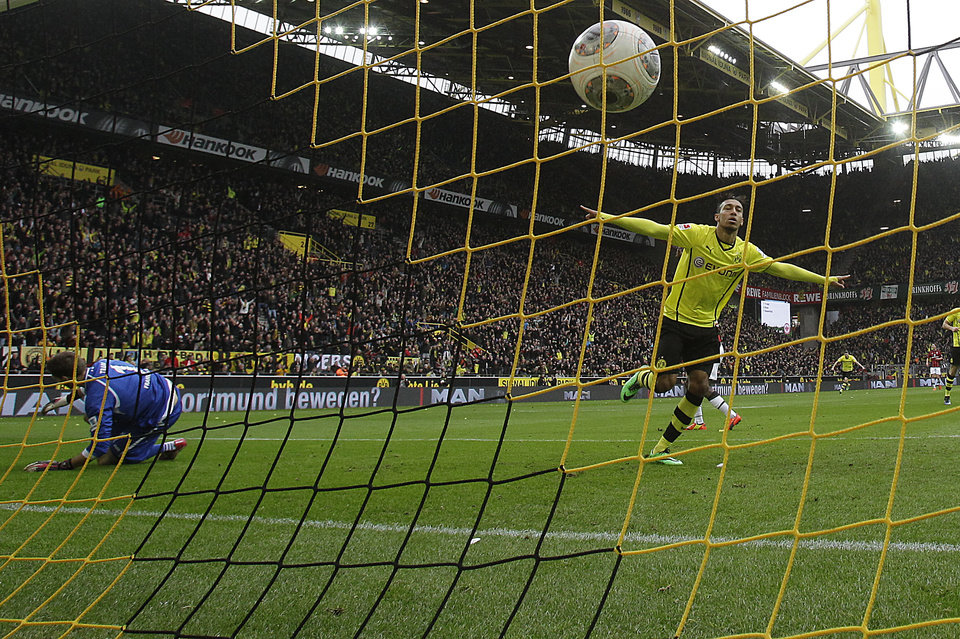 Photo - Dortmund's Pierre-Emerick Aubameyang of Gabon, right, celebrates after scoring against Frankfurt goalkeeper Kevin Trapp during the German first division Bundesliga soccer match between BvB Borussia Dortmund and Eintracht Frankfurt in Dortmund, Germany, Saturday, Feb. 15, 2014. (AP Photo/Frank Augstein)