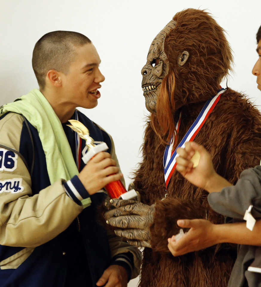 Photo -  Dru Anthony, left, and Ben McKensie, in costume, celebrate winning a competition award during the Oklahoma Native American Youth Language Fair on Tuesday at the Sam Noble Oklahoma Museum of Natural History. PHOTO BY STEVE SISNEY, THE OKLAHOMAN   STEVE SISNEY -