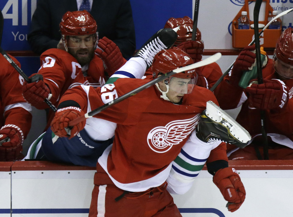 Photo - Detroit Red Wings right wing Tomas Jurco (26) checks Vancouver Canucks defenseman Alexander Edler of Sweden into the Red Wings bench during the first period of an NHL hockey game in Detroit, Monday, Feb. 3, 2014. (AP Photo/Carlos Osorio)