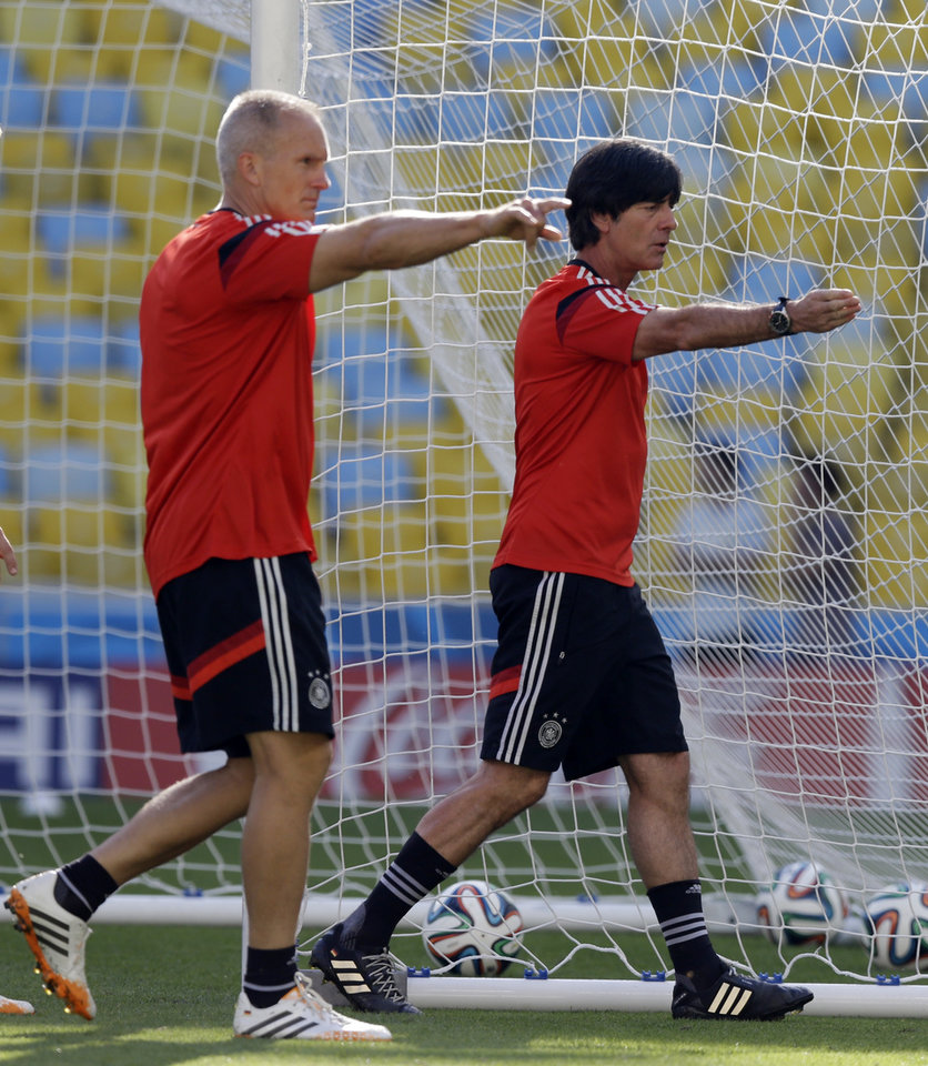 Photo - Germany's head coach Joachim Loew, right, with an assistant, check the pitch during an official training session a day prior to the quarter final World Cup soccer match between France and Germany at the Maracana stadium in Rio de Janeiro, Brazil, Thursday, July 3, 2014. (AP Photo/Thanassis Stavrakis)