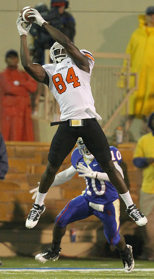 Photo - Oklahoma State's Hubert Anyiam (84) makes a catch over Tulsa's Justin Skillens (10) during a college football game between the Oklahoma State University Cowboys and the University of Tulsa Golden Hurricane at H.A. Chapman Stadium in Tulsa, Okla., Sunday, Sept. 18, 2011. Photo by Chris Landsberger, The Oklahoman
