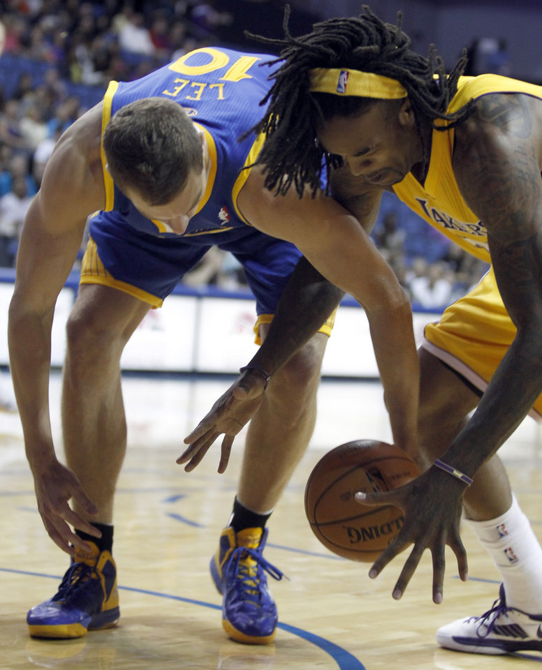 Photo - Golden State Warriors center David Lee, left, works against Los Angeles Lakers center Jordan Hill, right for the ball in the first quarter during an NBA basketball preseason game Saturday, Oct. 5, 2013, in Ontario, Calif.  (AP Photo/Alex Gallardo)