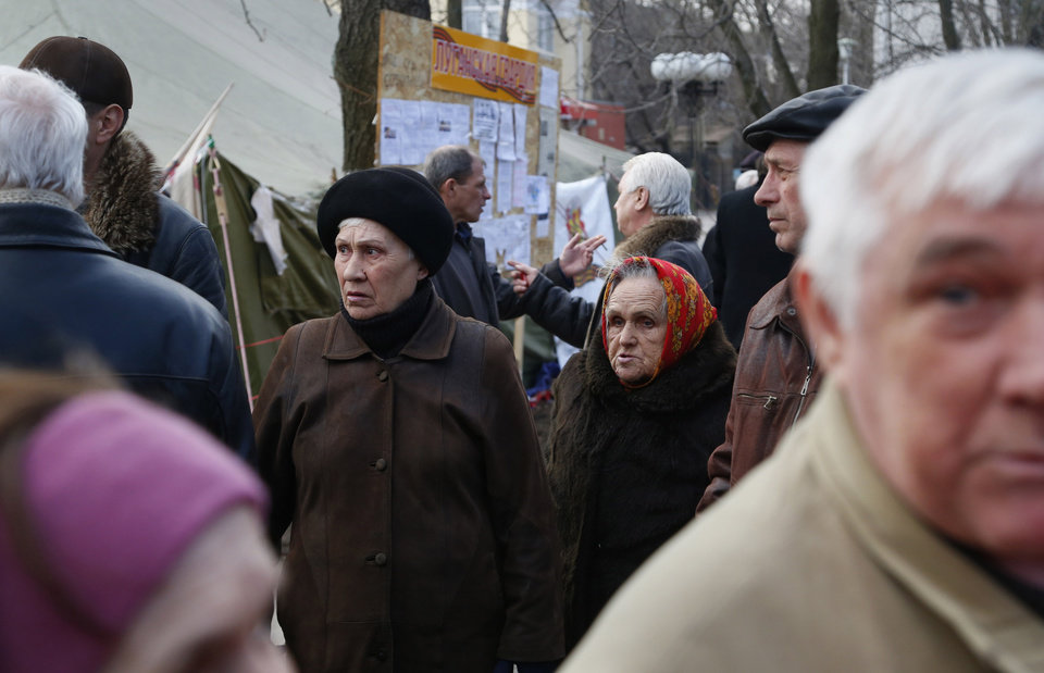 Photo - In this photo taken Tuesday, March 11, 2014, men debate as people gather in a pro Russian camp in Luhansk, eastern Ukraine. The breakup of the Soviet Union and harsh economic realities of the market haven't been kind to many local employers. Residents say many factories, including the locomotive works, have had to drastically cut both payrolls and production.  Since Russian troops rolled into Crimea, and lawmakers there scheduled a referendum for Sunday on whether to join Russia, the world's attention has focused on the fate of the lush peninsula that juts into the Black Sea. But here in Ukraine's coal-fired industrial east, where Russians have lived for more than two centuries, a potent mix of economic depression, ethnic solidarity and nostalgia for the certainties of the Soviet past have many demanding the right to become part of Russia as well (AP Photo/Sergei Grits)