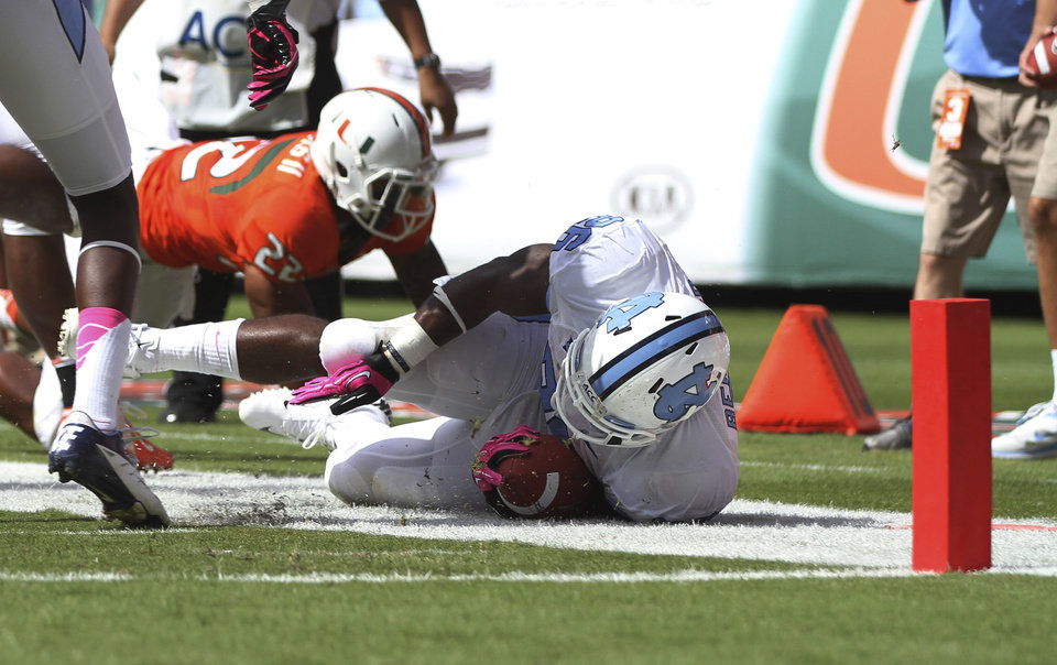 North Carolina's Giovani Bernard is stopped short of the goal by Miami Kacy Rodgers II (22) during the first half of a NCAA college football game in Miami, Saturday, Oct. 13, 2012. (AP Photo/J Pat Carter)