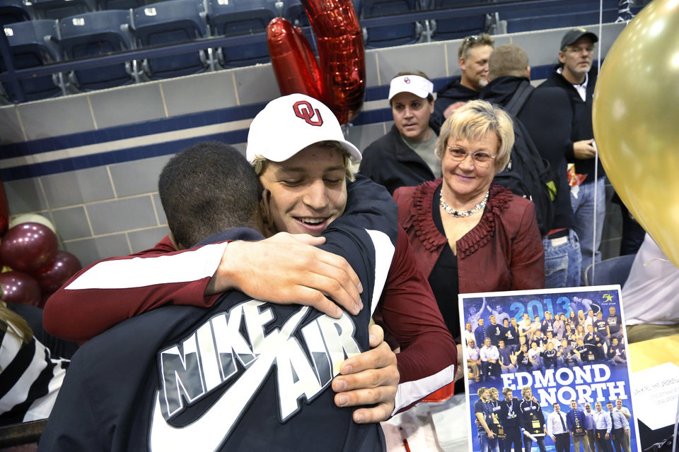 Lance Dixon is hugged by a fellow athlete after the signing ceremony in which Lance and his two brothers signed letters of intent with OU\'s wrestling team. Athletes from Edmond North High School signed national letters of intent with colleges and universities during a ceremony in the school\'s gymnasium Wednesday morning, Nov. 13, 2013. Various sports include golf, softball, wrestling, lacrosse and others. Photo by Jim Beckel, The Oklahoman