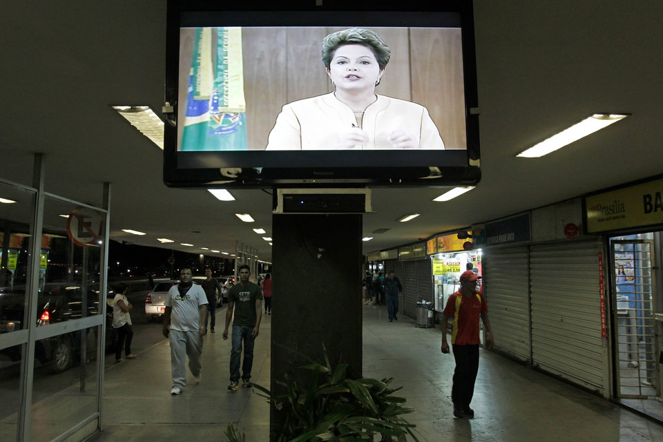 Photo - A message by Brazil's President Dilma Rousseff is broadcast live at the bus station in Brasilia, Brazil, Friday, June 21, 2013. The Brazilian ended her near-silence about more than a week of massive, violent protests, saying in a prime time TV broadcast Friday that peaceful demonstrations were part of a strong democracy but that violence could not be tolerated. She promised to make improvements to public services, but said it couldn't be done overnight. (AP Photo/Eraldo Peres)