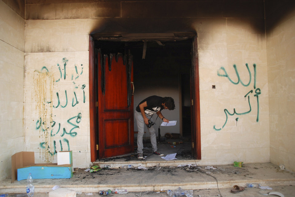 Photo -   FILE - In this Wednesday, Sept. 12, 2012 file photo, a man looks at documents at the U.S. consulate in Benghazi, Libya, after an attack that killed four Americans, including Ambassador Chris Stevens. The graffiti reads,