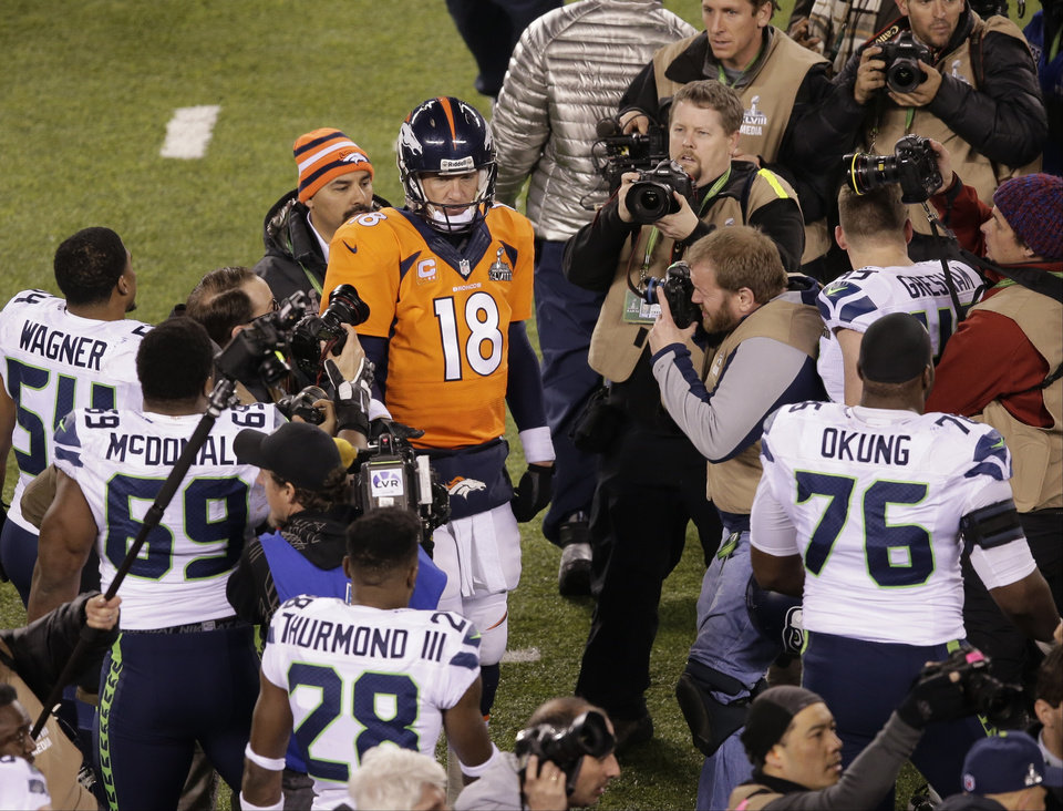 Photo - Denver Broncos' Peyton Manning (18) walks the field after the NFL Super Bowl XLVIII football game against the Seattle Seahawks Sunday, Feb. 2, 2014, in East Rutherford, N.J. The Seahawks won 43-8. (AP Photo/Charlie Riedel)