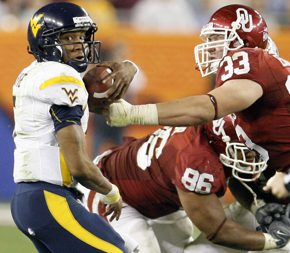 Photo - West Virginia's Patrick White (5) gets past Oklahoma's Adrian Taylor (86) and Auston English (33) during the first half of the Fiesta Bowl college football game between the University of Oklahoma Sooners (OU) and the West Virginia University Mountaineers (WVU) at The University of Phoenix Stadium on Wednesday, Jan. 2, 2008, in Glendale, Ariz. 
