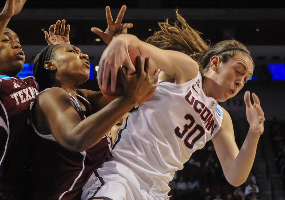 Photo - Texas A&M's Karla Gilbert (34) and Connecticut's Breanna Stewart (30) battle for a rebound during the first half of their  regional final in the NCAA college basketball tournament in Lincoln, Neb., Monday March 31, 2014. (AP Photo/Dave Weaver)