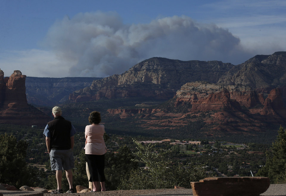 Photo - Tourists watch the Slide Fire from a scenic overlook as it burns up Oak Creek Canyon nearby on Thursday, May 22, 2014, in Sedona, Ariz.  The fire has burned approximately 4,800 acres. (AP Photo/Ross D. Franklin)