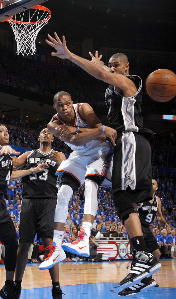 Photo - NBA BASKETBALL: Oklahoma City's Russell Westbrook (0) passes the ball around San Antonio's Tim Duncan (21) during Game 3 of the Western Conference Finals between the Oklahoma City Thunder and the San Antonio Spurs in the NBA playoffs at the Chesapeake Energy Arena in Oklahoma City, Thursday, May 31, 2012.  Photo by Sarah Phipps, The Oklahoman
