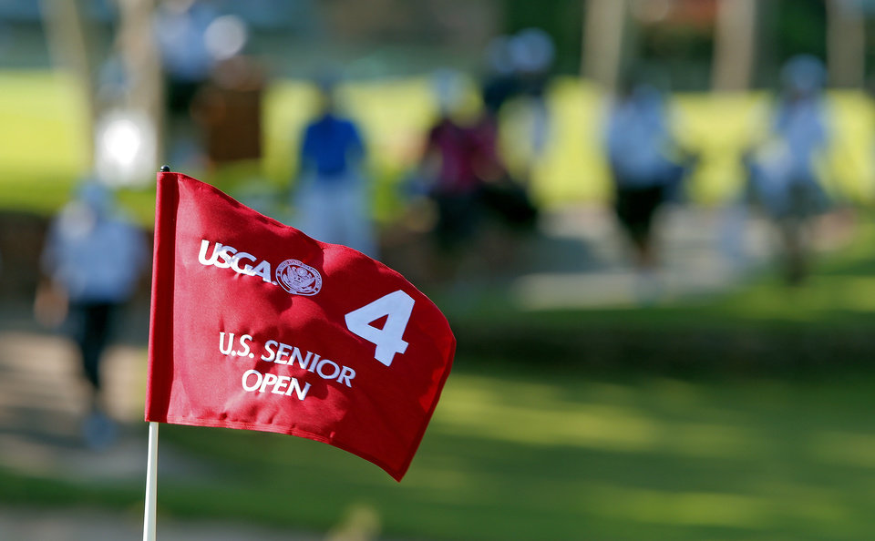 Photo - The flag on the fourth green waves in the wind during practice rounds for the U.S. Senior Open golf tournament at Oak Tree National in Edmond, Okla. on Monday, July 7, 2014. Photo by Chris Landsberger, The Oklahoman