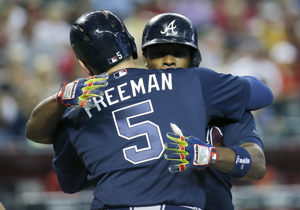 Photo - Atlanta Braves' Justin Upton embraces teammate Freddie Freeman (5) after hitting a two run home run against the Arizona Diamondbacks during the sixth inning of a baseball game, Sunday, June 8, 2014, in Phoenix. (AP Photo/Matt York)