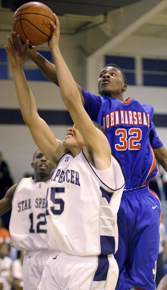 Photo - John Marshall's Tavion Fleeks goes for the ball over John Cooksey of Star Spencer during a high school basketball game at Star Spencer in Spencer, Okla., Tuesday, December 8, 2009.  Photo by Bryan Terry, The Oklahoman ORG XMIT: KOD