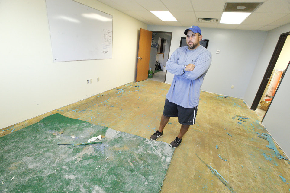 Photo - Coach Greg Wallis stands with the remains of his office in the field house at Bridge Creek High School in Bridge Creek Monday, Aug. 11, 2014.  Vandals spread paint, carpet glue, and rat poison on football equipment and furniture throughout the building. Carpets had to be removed and many items placed in the trash leaving Bridge Creek without enough helmets, jerseys and other equipment .  Photo by Paul B. Southerland, The Oklahoman