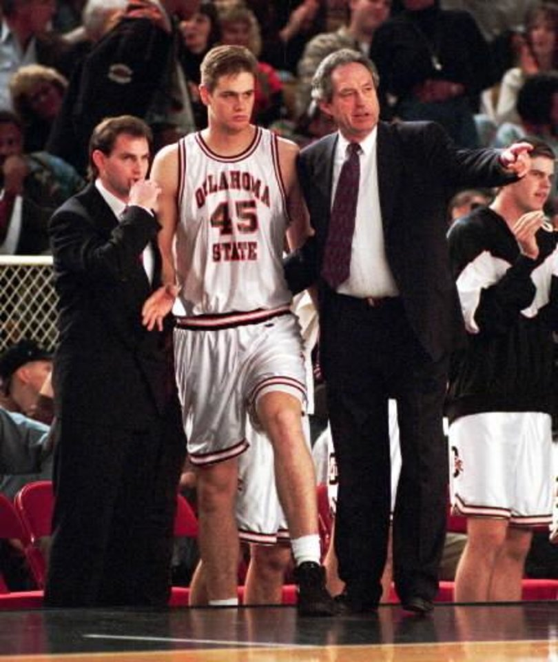 Eddie Sutton, right, gives instructions to John Nelson as assistant coach Sean Sutton listens in this 1994 photo.